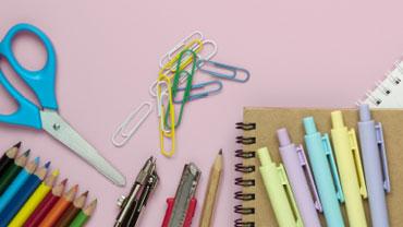 Bunte Schreibwaren auf einem rosafarbenen Tisch
