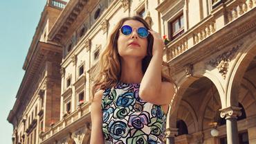 Gebräunte Frau mit blauer Sonnenbrille und Blumenkleid steht vor italienischer Architektur