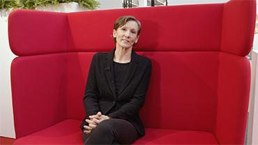 Trendexpertin Gabriela Kaiser sitzt auf einem roten Sofa zum Interview