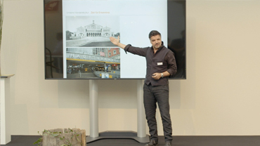 Stefan Suchanek steht erklärend auf der Bühne vor einem Monitor