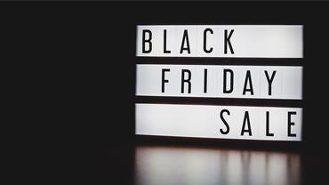"""Ein Leuchtkasten mit der Aufschrift """"Black Friday Sale"""" steht im Dunkeln."""