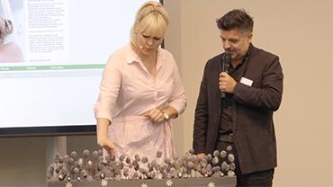 Victoria Salomon und Moderator Stefan Suchanek präsentieren ein Gesteck aus grauen Tannenzapfen.