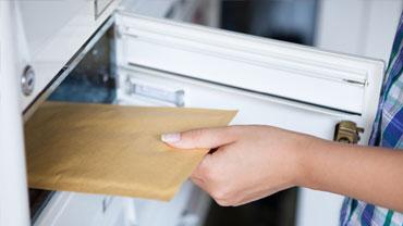 Eine Hand holt einen Briefumschlag aus einem Briefkasten