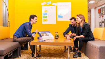 Eine Teambesprechung in einem gelb gestrichenen, modernen Büroraum