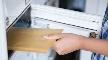 A hand is removing a padded envelope from the letter box