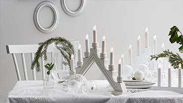 A white table set with electric candles and evergreen boughs