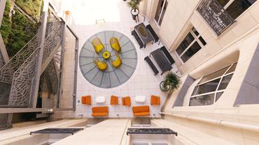 Vogelperspektive eines Innenhofs mit Sitzgelegenheiten in Orange und Gelb