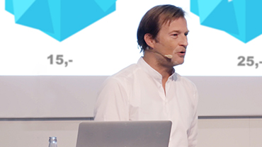 Retail-Kommunikationsexperte Björn Lockstein hält einen Vortrag vor einer Projektion.