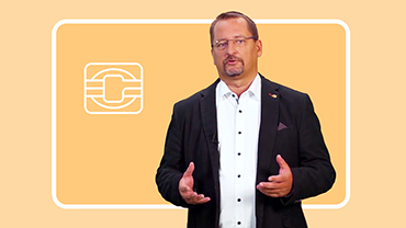 Jörg Stahl referiert vor dem gelben Hintergrund einer stilisierten Kreditkarte.