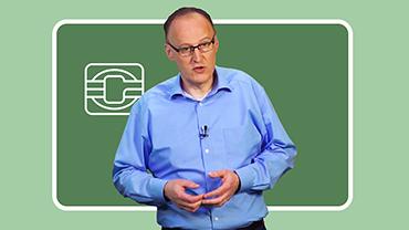 Dr. Thomas Denny referiert vor einem grünen Hintergrund