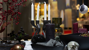 Table with vases, decorative elements and candlesticks in dark colors