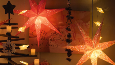 Two red and yellow shining stars hang from the ceiling, behind it a picture with lettering, next to it a Christmas tree frame with candles