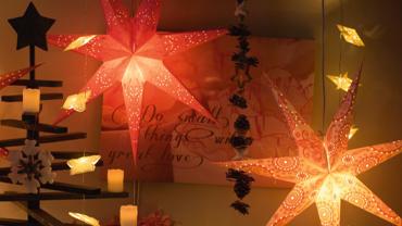 Zwei rot gelbe leuchtende Sterne hängen von der Decke, dahinter ein Bild mit Schriftzug, daneben ein Christbaumgestell mit Kerzen