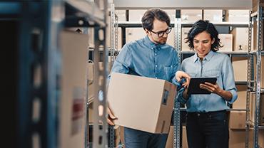 Mann und Frau, beide im blauen Hemd, stehen mit einem Tablet und einem Karton zwischen Regalen mit vielen Kartons