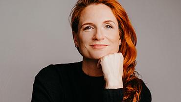 Retail-Expertin Katrin Gugl vor grauem Hintergrund