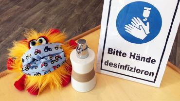 Ein Plüsch Virus mit Mundschutz, ein Desinfektionsspender und ein Schild mit Corona Hygiene Hinweisen.