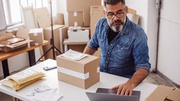 Ein Mann mit Bart und blauem Jeans Hemd sitzt mit Laptop an seinem Schreibtisch und verpackt Pakete