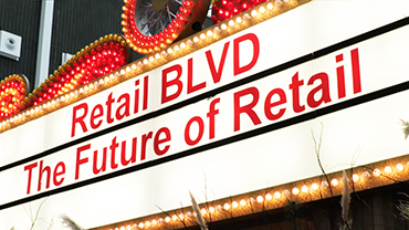 """An illuminated advertisement in red letters reading """"Retail BLVD – The Future of Retail""""."""