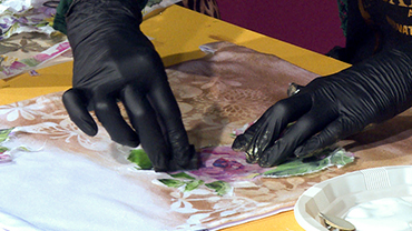 Ein Händepaar in schwarzen Einweghandschuhen appliziert einen Rosendruck auf eine Stofftasche.