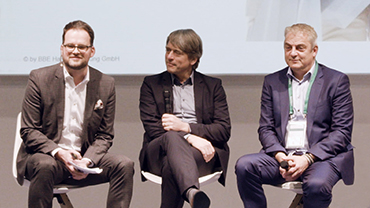 Sebastian Deppe, Martin Kremming und Daniel Schnödt diskutieren auf einer Bühne vor einer Projektion.