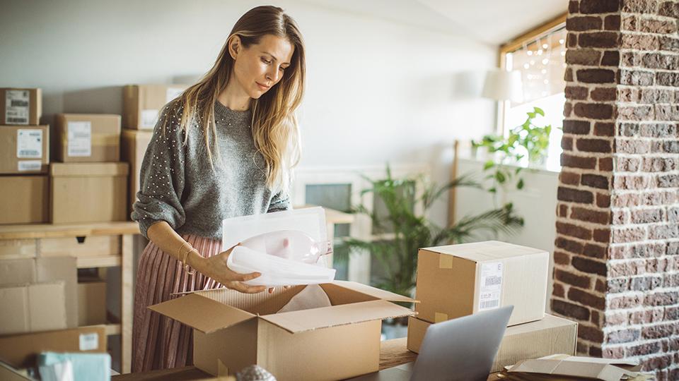 Junge Frau packt eine Vase zum Versand in einen Karton. Daneben stehen weitere Kartons und ihr Laptop.